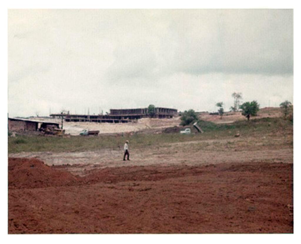 Año 1964. El diseñador Mark Mahannah camina por el campo durante una visita de inspección. La imagen capta los terrenos que hoy ocupan los hoyos 17, 15 y 14. Al fondo se aprecian las obras de construcción de la sede social. Arriba a la derecha aparece la explanada que ocuparán las canchas de tenis.
